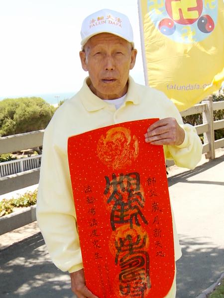 85歲的王秀林特意帶著一副用篆體書寫的「鶴壽」來到集會現場。(鄭浩/大紀元)