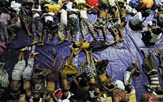 2015年5月12日,印尼救援人员营救了亚齐省水域载有573缅甸和孟加拉国罗辛亚人难民的船只,图为难民在政府体育礼堂。近2000名缅甸和孟加拉国船民已获救,或是游过岸到达马来西亚和印度尼西亚。当局警告说更多绝望的难民可能在海上。(CHAIDEER MAHYUDDIN/AFP)
