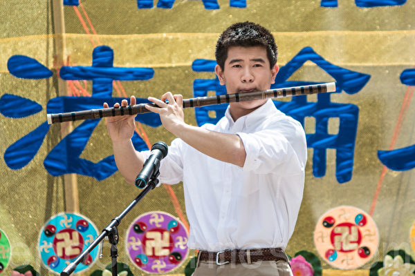 5月13日,法輪功學員在紐約富利廣場演出慶祝第16屆「世界法輪大法日」。圖為加州飛天藝術學校的高橋在表演笛子獨奏。(馬有志/大紀元)