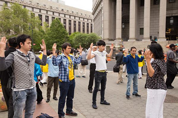 5月13日,法輪功學員紐約富利廣場煉功。煉功的祥和場面,吸引路人在現場學動作。(戴兵/大紀元)