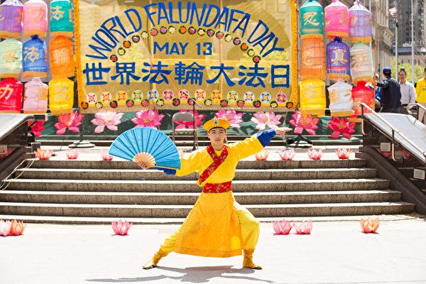 5月13日,法輪功學員在紐約富利廣場演出慶祝第16屆「世界法輪大法日」。圖為加州飛天藝術學校學生在表演獨舞「青年康熙」。(戴兵/大紀元)
