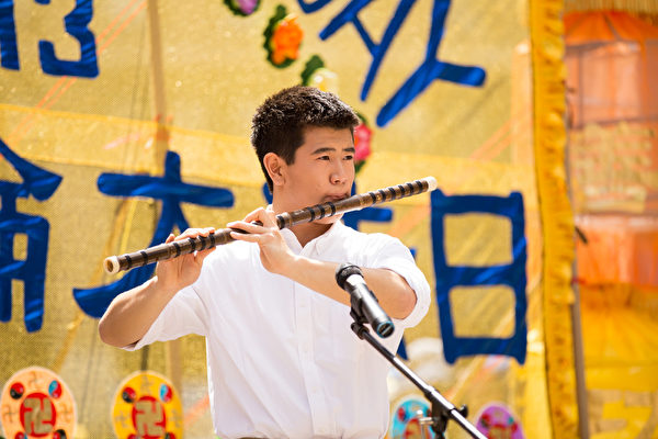 5月13日,法輪功學員在紐約富利廣場演出慶祝第16屆「世界法輪大法日」。圖為加州飛天藝術學校的高橋在演奏笛子獨奏。(戴兵/大紀元)