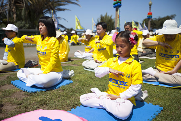 慶祝法輪大法日,洛杉磯學員在聖莫妮卡碼頭公園集體煉功。(季媛/大紀元)