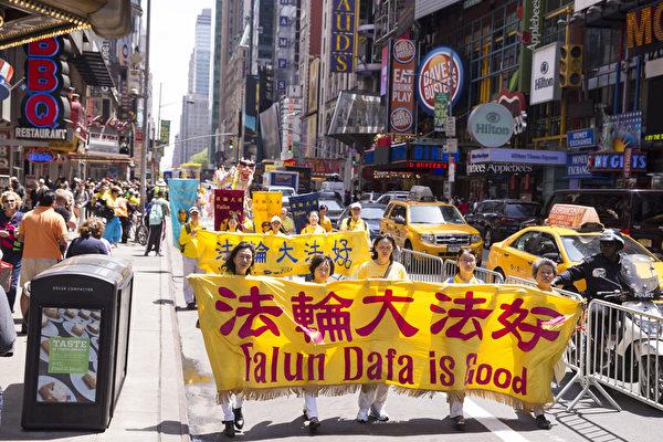 """5月15日,8千多名来自全世界50多个国家200多个地区的部分法轮功学员齐聚纽约市曼哈顿,沿着纽约中心42街,举行声势浩大的游行。图为游行第一方阵""""法轮大法好""""。(戴兵/大纪元)"""