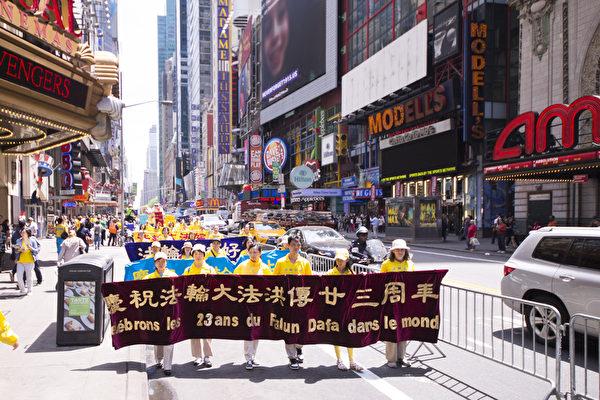 """5月15日,8千多名来自全世界50多个国家200多个地区的部分法轮功学员齐聚纽约市曼哈顿,沿着纽约中心42街,举行声势浩大的游行。图为游行第一方阵""""法轮大法好""""-法轮大法洪传世界。(戴兵/大纪元)"""