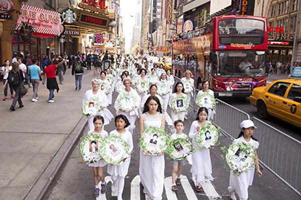 """5月15日,8千多名来自全世界50多个国家200多个地区的部分法轮功学员齐聚纽约市曼哈顿,沿着纽约中心42街,举行声势浩大的游行。图为游行第二方阵""""停止迫害法轮功""""-悼念被迫害死的大法弟子。(戴兵/大纪元)"""
