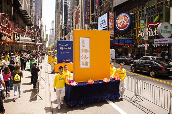 """5月15日,八千多名来自全世界50多个国家200多个地区的部分法轮功学员齐聚纽约市曼哈顿,沿着纽约中心42街,举行声势浩大的游行。图为游行第一方阵""""法轮大法好""""-《转法轮》书模型。(爱德华/大纪元)"""