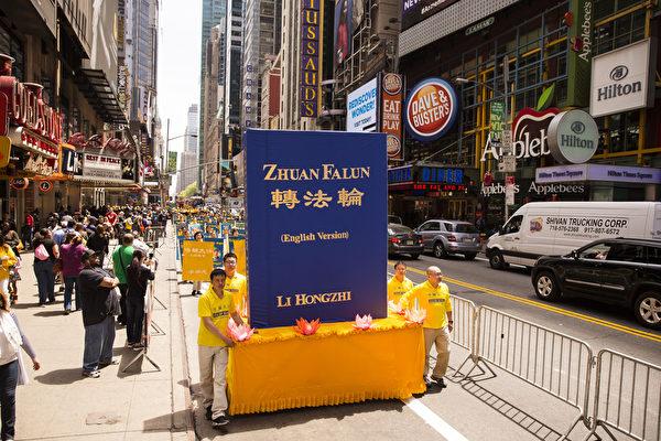 """5月15日,八千多名来自全世界50多个国家200多个地区的部分法轮功学员齐聚纽约市曼哈顿,沿着纽约中心42街,举行声势浩大的游行图为游行第一方阵""""法轮大法好""""-《转法轮》书模型 。(爱德华/大纪元)"""