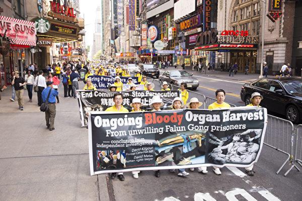 """5月15日,8千多名来自全世界50多个国家200多个地区的部分法轮功学员齐聚纽约市曼哈顿,沿着纽约中心42街,举行声势浩大的游行。图为游行第二方阵""""停止迫害法轮功""""。(戴兵/大纪元)"""