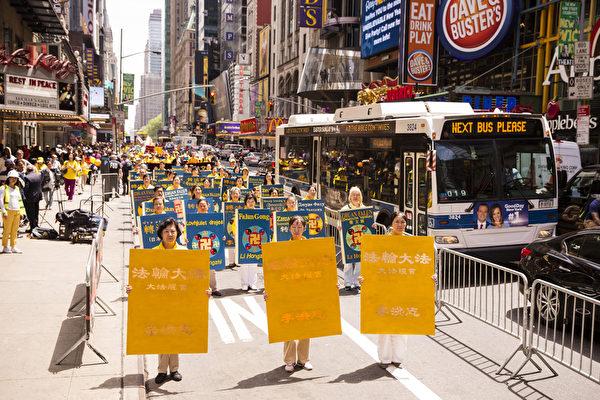 """5月15日,八千多名来自全世界50多个国家200多个地区的部分法轮功学员齐聚纽约市曼哈顿,沿着纽约中心42街,举行声势浩大的游行。图为游行第一方阵""""法轮大法好""""-《转法轮》书模型,翻译成各国语言。(爱德华/大纪元)"""
