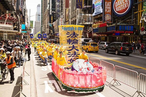 """5月15日,八千多名来自全世界50多个国家200多个地区的部分法轮功学员齐聚纽约市曼哈顿,沿着纽约中心42街,举行声势浩大的游行。图为游行第一方阵""""法轮大法好""""-大花船。(爱德华/大纪元)"""