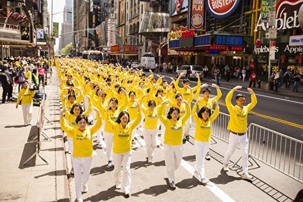 """5月15日,八千多名来自全世界50多个国家200多个地区的部分法轮功学员齐聚纽约市曼哈顿,沿着纽约中心42街,举行声势浩大的游行。图为游行第一方阵""""法轮大法好""""-法轮功功法展示。(爱德华/大纪元)"""