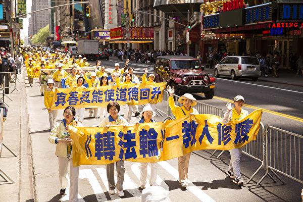 """5月15日,八千多名来自全世界50多个国家200多个地区的部分法轮功学员齐聚纽约市曼哈顿,沿着纽约中心42街,举行声势浩大的游行。图为游行第一方阵""""法轮大法好""""(爱德华/大纪元)"""