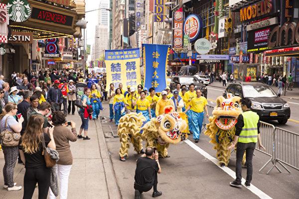 """5月15日,8千多名来自全世界50多个国家200多个地区的部分法轮功学员齐聚纽约市曼哈顿,沿着纽约中心42街,举行声势浩大的游行。图为游行第三方阵""""声援2亿中华儿女退出中共""""-舞狮。(戴兵/大纪元)"""