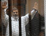 """美国国务院关于2015年5月17日表示,美国对埃及法院判处前总统、也是首位民选总统穆尔西死刑""""深表关切""""。本图为穆尔西于1月8日,仍被囚困在法庭笼中内接受审判。 (STR/AFP/Getty Images)"""