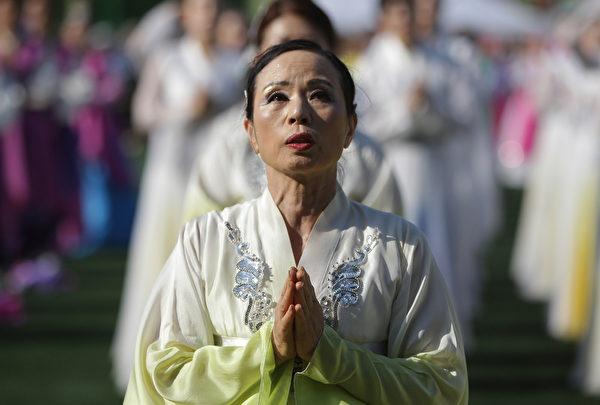 2015年5月16日,韩国首尔,庆祝佛祖诞辰,参加彩灯游行的民众双手合十祈福。(Chung Sung-Jun/Getty Images)
