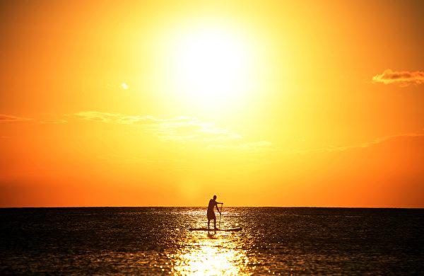 巴巴多斯全年平均日照时间达3,000小时。图为1位游客划冲浪桨在布里奇海滩附近。(JEWEL SAMAD/AFP)