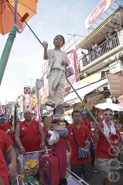 小朋友扮演强推政改方案的政务司司长林郑月娥,有村民为她离地撑伞。(余钢/大纪元)