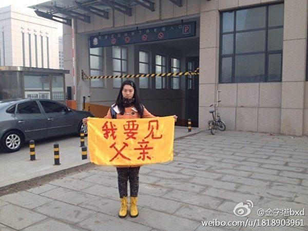 23歲的唐山女孩卞曉輝3月12日上午9點左右,與陳英華再次在街頭打橫幅——「我要見父親」,在寒風中表達自己的訴求。(網絡圖片)