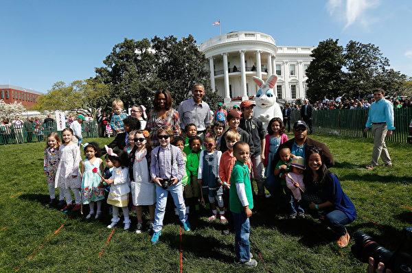 """2014年4月21日,美国总统奥巴马夫妇在白宫南草坪,主持第136回一年一度的""""快乐复活节滚彩蛋""""活动。图为奥巴马夫妇与参加者合影。(Win McNamee/Getty Images)"""