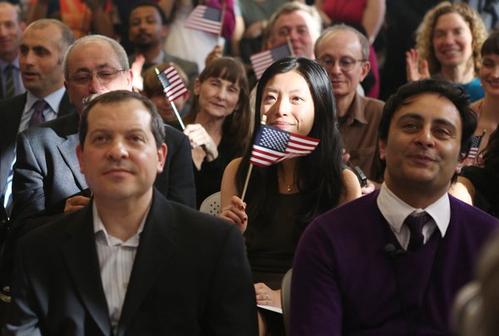 """今年美国独立日期间,美国将举办50场入籍宣誓仪式。据美国人口普查局最新统计,亚裔移民是归化率最高的族群。图为中国移民Yi Shu(中)参加2013年在纽约""""租户博物馆""""举办的入籍仪式。(大纪元)"""