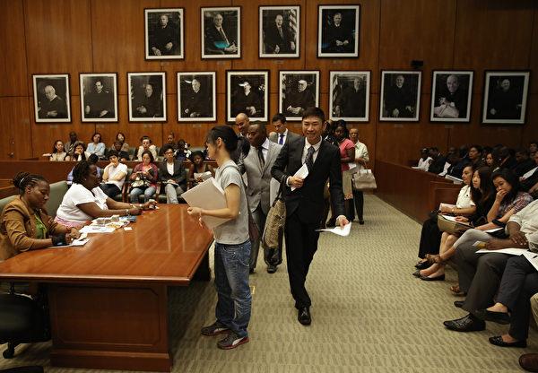 2013年,纽约布鲁克林区法院共为77,000位移民举办入籍仪式。图为新公民正在交还他们的绿卡。(John Moore/Getty Images)