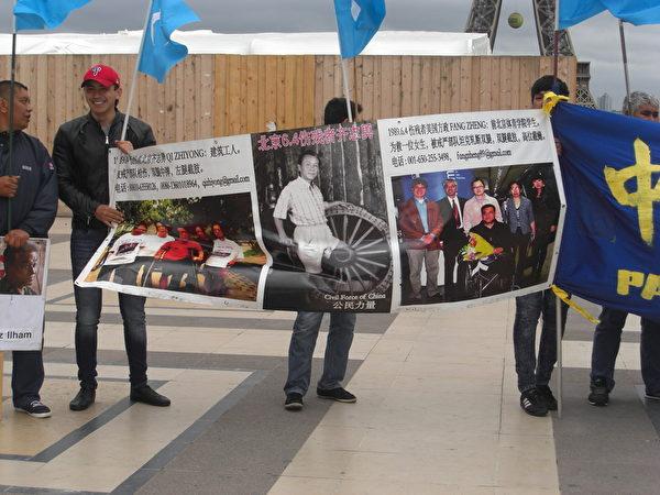在广场上,与会者举著各种大型横幅和旗帜,其中两幅大型照片特别让人注目。(大纪元)