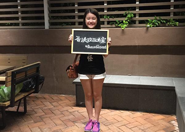 """18岁的港大文学院学生张小姐,参加悼念六四活动后,还手持""""否决政改方案""""纸牌拍照,为否决政改出一份力。(梁珍/大纪元)"""