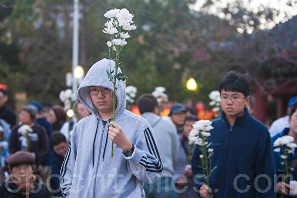 """6月3日晚,旧金山各界民众在中国城的花园角举办题为""""从未忘记,永不放弃""""的六四26周年纪念烛光晚会。今年的纪念活动的特点,是有更多的80后、90后年轻人参与。图为民众在献花。(马有志/大纪元)"""