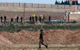 圖為2015年6月15日,一名土耳其士兵走在土耳其邊境,對面則是敘利亞邊境,庫爾德戰士(YPG)攻佔塔爾艾卜耶德後揮舞著旗幟。(Gokhan Sahin/Getty Images)