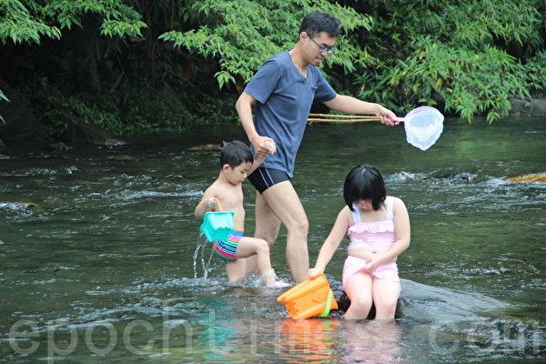 亲子于水潭中戏水。(谢月琴/大纪元)