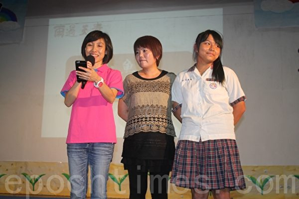 达不到毕业标准的毕业生陈映雪(右) 感谢校长林家如(左)以鼓励和争取补考机会让她和其他3位同学能顺利拿到毕业证书。中为家长会长夫人苏柔蓉。(林萌骞/大纪元)