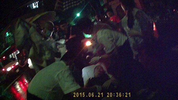 嘉义市一名33岁孕妇21日晚间骑机车,与一辆轿车发生擦撞,倒地受伤;由于当时正下着雨,附近居民见状,立即为她撑伞。(嘉义市消防局提供)