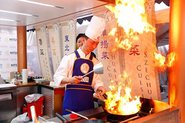 2015年6月27日,第七届新唐人全世界中国菜厨技大赛决赛正式在纽约时代广场隆重开场。川菜选手朱军正在密锣紧鼓的准备菜式。(戴兵/大纪元)