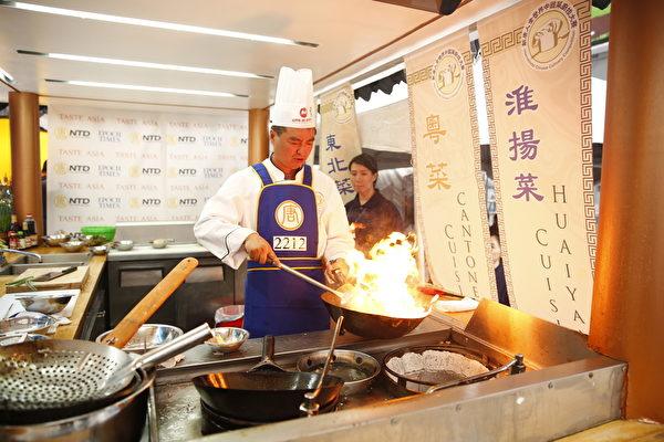 2015年6月27日,第七屆新唐人全世界中國菜廚技大賽決賽正式在紐約時代廣場隆重開場。圖為東北菜優秀獎得主張濟光在準備參賽的菜目「滑炒裡脊絲」、「尖椒乾豆腐」。(戴兵/大紀元)