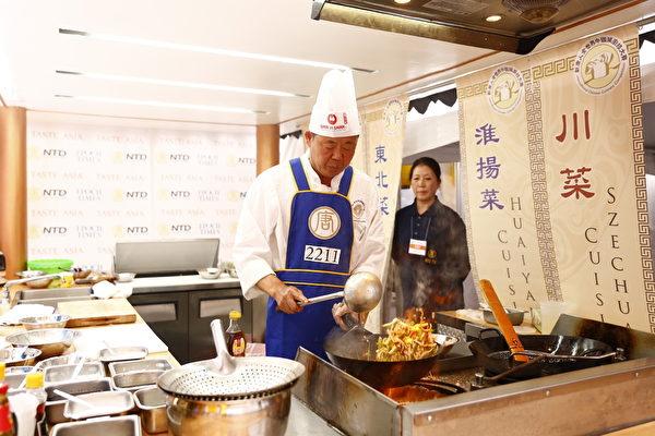 2015年6月27日,第七屆新唐人全世界中國菜廚技大賽決賽正式在紐約時代廣場隆重開場。圖為東北菜銅獎得主嚴哲在準備參賽的菜目「滑炒裡脊絲」、「尖椒乾豆腐」。(戴兵/大紀元)