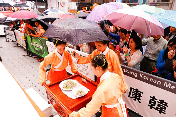 6月27日,第七届新唐人全世界中国菜厨技大赛决赛在纽约时代广场举行。当天下午下起了雨,观众打伞观看比赛,不愿离去。(戴兵/大纪元)