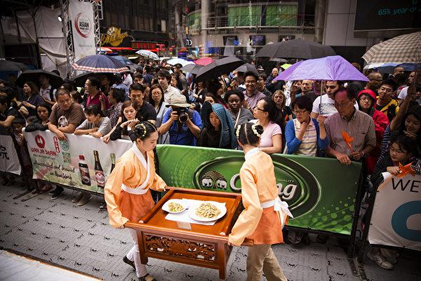 6月27日,第七屆新唐人世界中國菜廚技大賽決賽在紐約時代廣場舉行,觀眾冒雨觀看。(愛德華/大紀元)