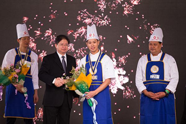 6月27日,第七屆新唐人全世界中國菜廚技大賽決賽在紐約時代廣場落幕。圖為新唐人電視台總裁唐忠(左二)為獲銀獎的選手溫禧明(中)頒獎。(戴兵/大紀元)