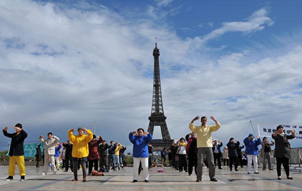 2012年4月24日,法國巴黎法輪功學員在艾菲爾鐵塔前煉功,向世人展示法輪功的美好。(本杰明/大紀元)