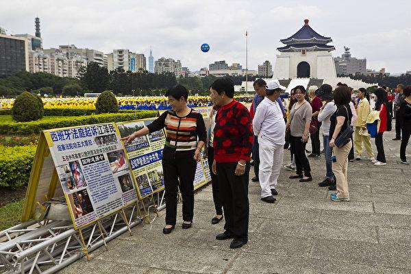 法輪功學員在台北自由廣場舉行排字弘法講真相活動,來往民眾駐足了解法輪功真相。(王嘉益/大紀元)