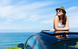 轻松快乐的女人在夏季旅游度假海岸倚在汽车天窗与背景的大海。(fotolia)