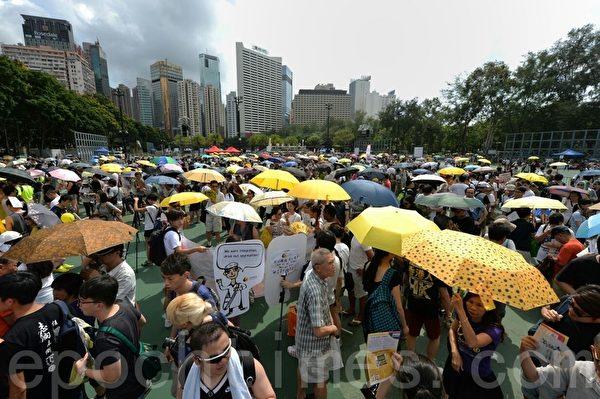 七一大游行维园现场,延续雨伞运动部分参与者手持黄伞。(潘在殊/大纪元)