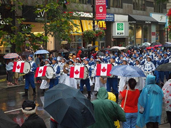蒙特利尔部分法轮功学员组成的天国乐团以及法轮功方阵,作为国庆游行阵的头阵,参加了今年蒙特利尔的加拿大国庆游行。(Nathalie Dieul / 大纪元)
