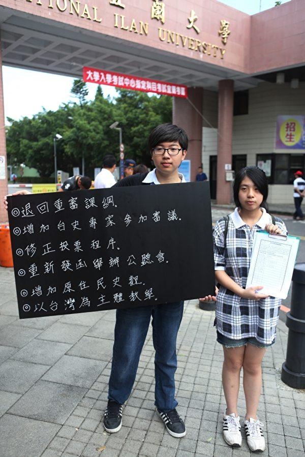 """王乙恩(右)、陈柏瑜(左)在宜大门口向学生说明""""课纲违调诉求""""并征求签名。(曾汉东/大纪元)"""