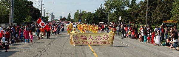 二零一五年七月一日下午,多伦多法轮功学员组成的天国乐团和腰鼓队赶场,又参加四点在大多伦多士嘉堡市举行的国庆节游行。(明慧网)