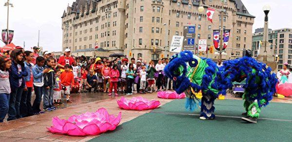 二零一五年加拿大国庆日,法轮功学员表演舞狮,与民众分享节日快乐。(明慧网)