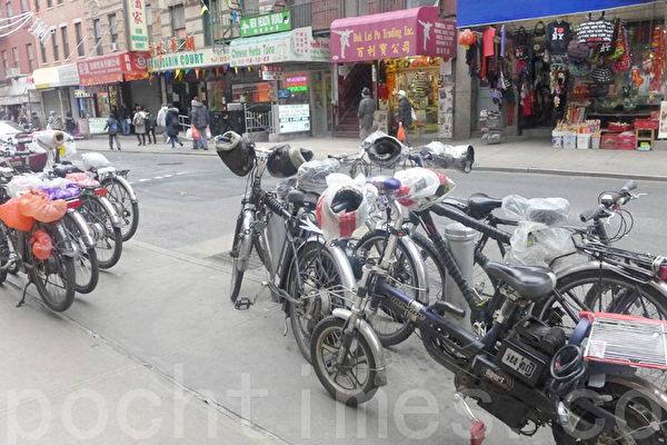 图为2013年市交通局在纽约华埠中华公所大礼堂举行了送货单车新法讲座时,外卖郎在中华公所门外停留的各式电单车。(蔡溶/大纪元)