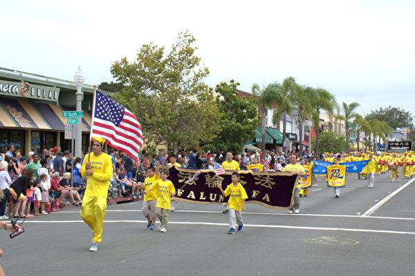 图:法轮功学员的队伍包括横幅、腰鼓队和花车。西人法轮功学员举着星条旗开道。(杨婕/大纪元)