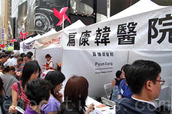 许多华人来到扁康医院的摊位前等待徐孝锡院长的义诊。(孙华/大纪元)